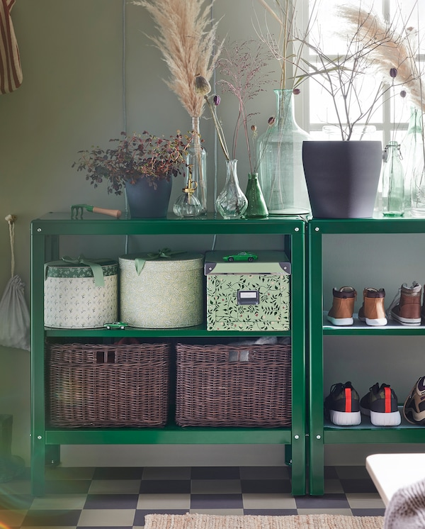 Dos estanterías con adornos en los estantes superiores y cajas, zapatos y cestas de ratán en los estantes inferiores.