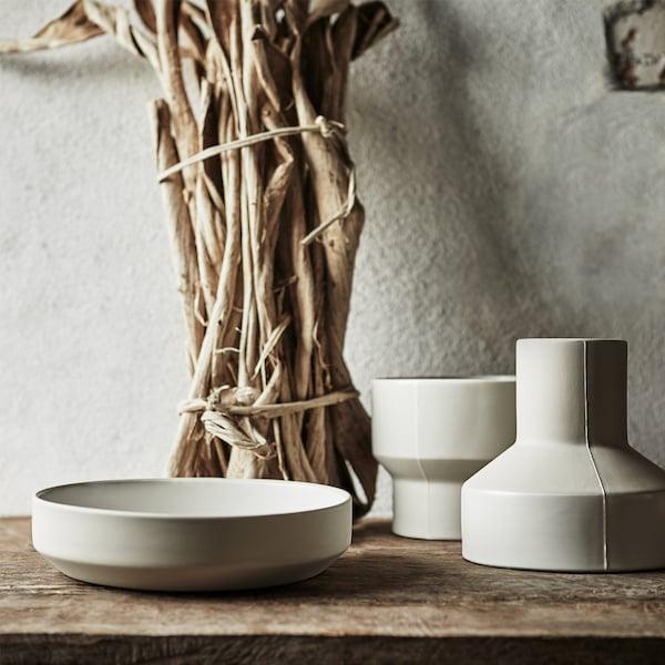 Dos jarrones de cerámica hechos a mano en gris claro y un cuenco ancho y bajo de la colección IKEA HANTVERK.