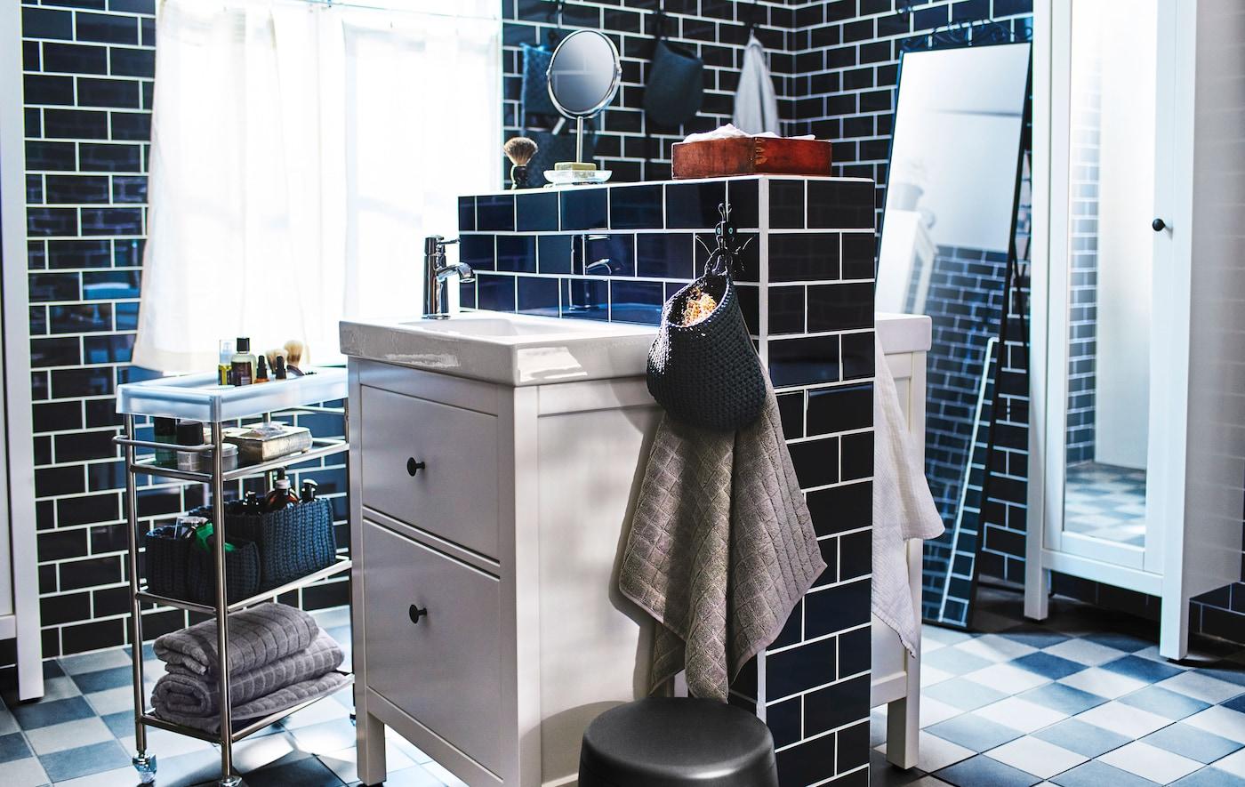 Dos lavabos de baño cuyas partes traseras se montan una contra la otra en el centro de un gran baño de azulejos negros.