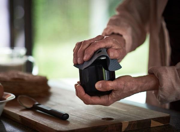 Dos manos sujetan un mango antideslizante para abrir tarros OMTÄNKSAM hecho de silicona suave y antideslizante que te ayuda a abrir ese tarro difícil.