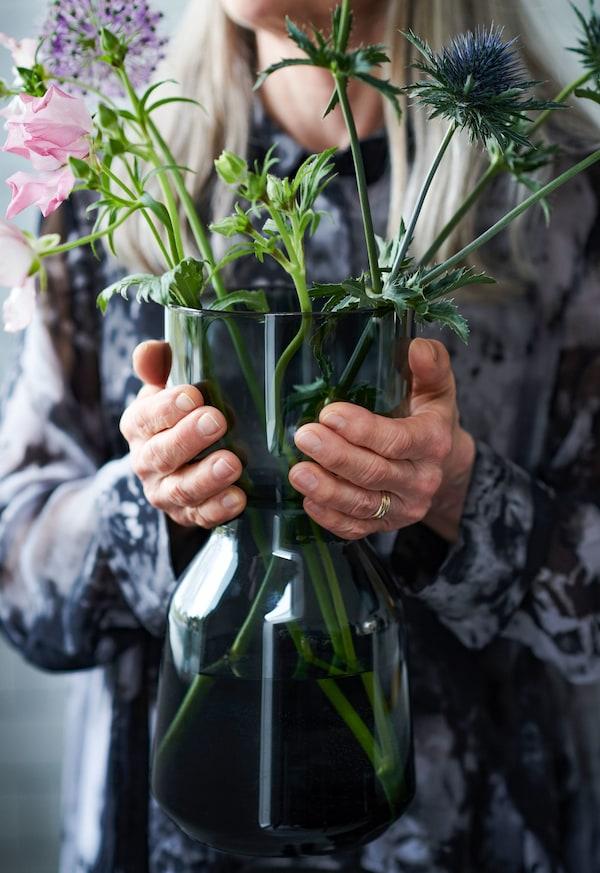 Dos manos sujetando un jarrón OMTÄNKSAM fácil de sujetar en vidrio verde oscuro lleno con flores.