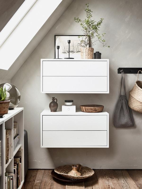 Dos módulos de pared blancos con artículos decorativos pequeños encima.
