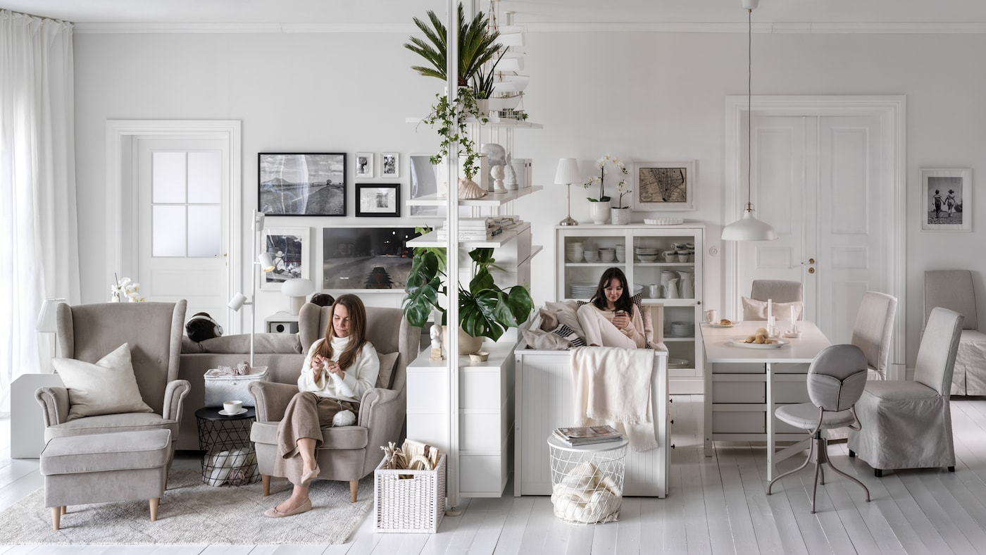 Dos mujeres sentadas, una en un sillón STRANDMON beige, a ambos lados de un módulo de almacenaje ELVARLI en un salón luminoso y amplio.