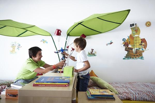 Dos niños juegan sobre el armario que divide su dormitorio.