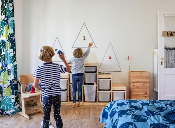 Dos niños jugando en un dormitorio con módulos de almacenaje para los juguetes en la pared.