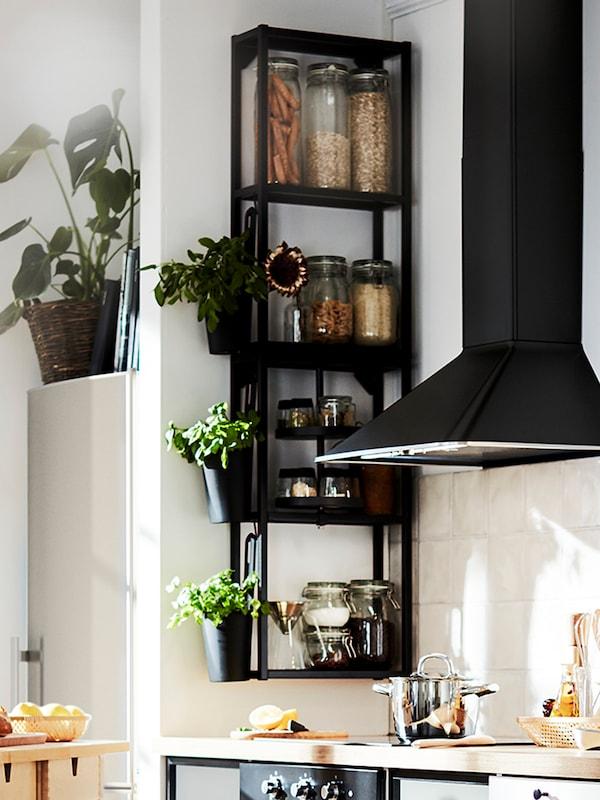 Două cadre suspendate ENHET, negre, cu polițe, montate pe un perete din colțul bucătăriei, lângă o hota aspirantă neagră, montată pe perete.