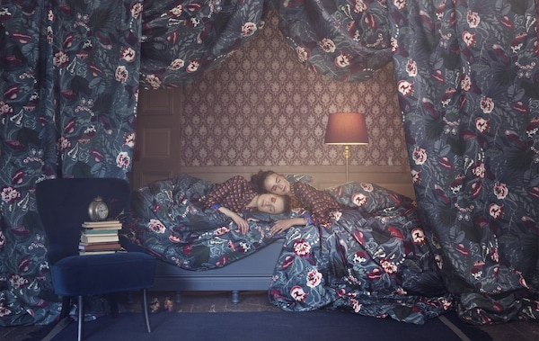 Două femei așezate pe un pat, cu tapet cu model, înconjurate de țesături cu motive florale.