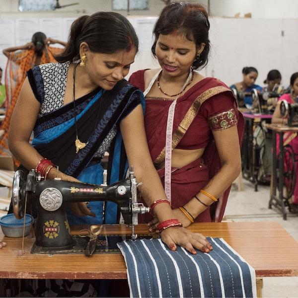 Două femei se bucură de un tutorial privind cusutul în cadrul inițiativei IKEA  de Ziua Internațională a Femeii din India.