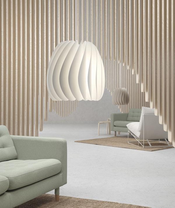 Două lustre suspendate într-o cameră cu canapele verzi pal și decorațiuni cu lambriuri din lemn.