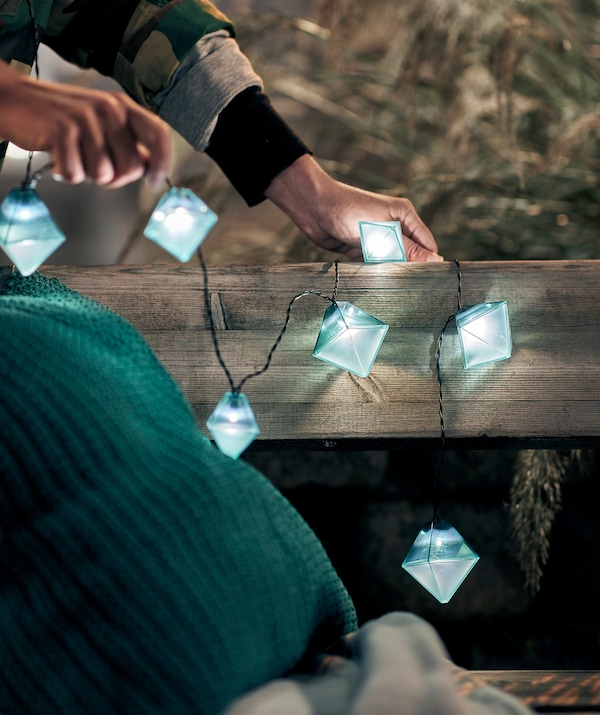 Două mâini decorând cu o ghirlandă luminoasă SOLVINDEN o bancă publică.  Pe bancă, o pernă de șezut și o pătură.