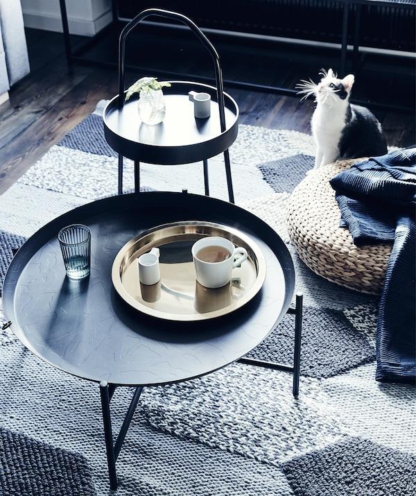 Două mese auxiliare închise la culoare și un taburet din ratan pe un covor texturat gri.