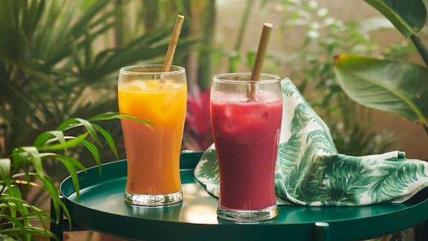 Două pahare cu mixuri de smoothie-uri FRUKSTUND pre-amestecate, unul din fructe galbene tropicale și altul din fructe roșii, așezate pe o masă printre plante.