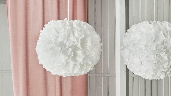 Două plafoniere VINDKAST albe în formă de pompon atârnă deasupra unei mese verzi cu o perdea roz în fundal.