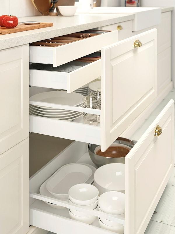 Două sertare de bucătărie în nuanțe de alb cu două sertare mai mici în cel de sus și unelte de gătit depozitate în cel de jos.
