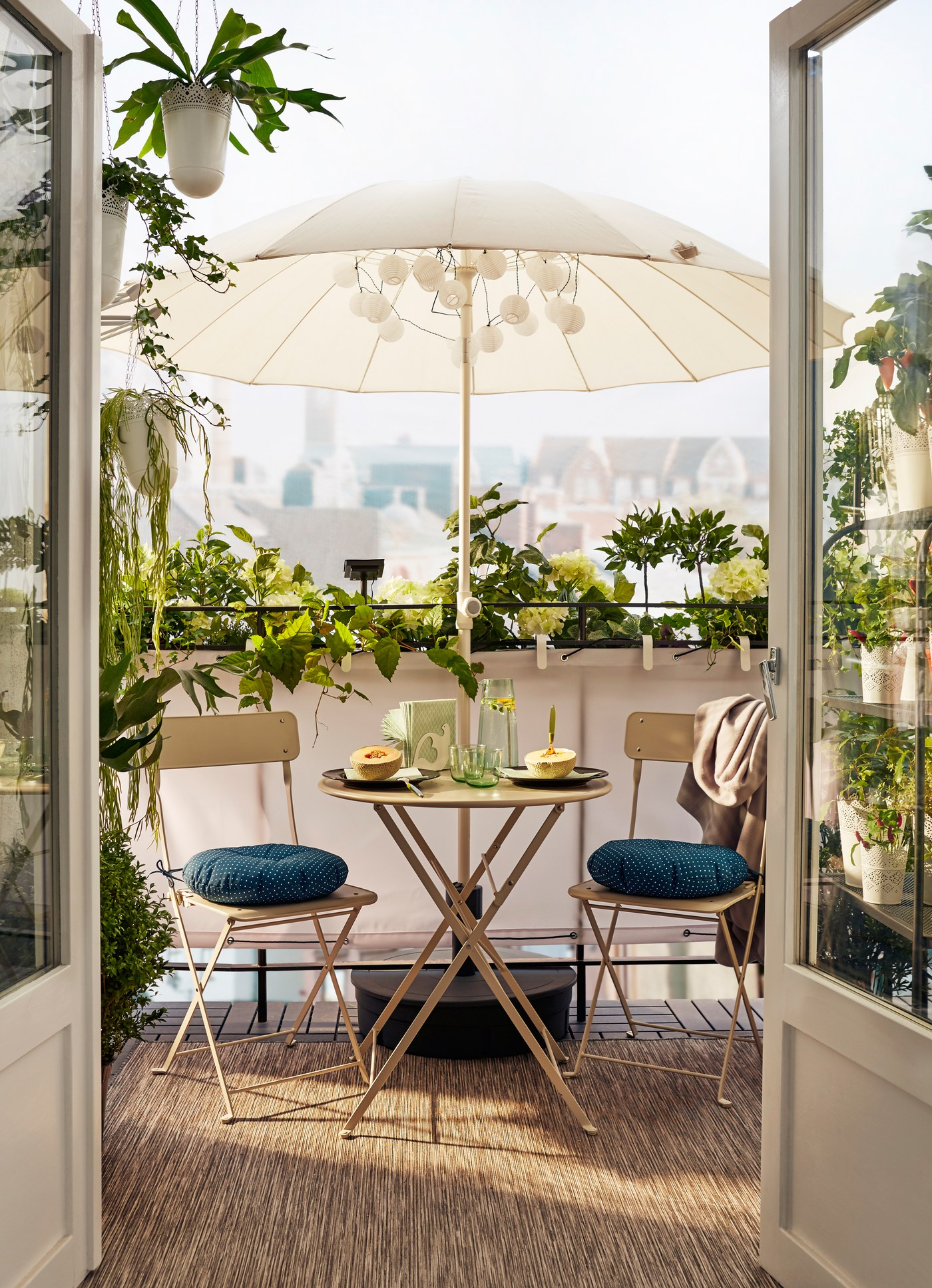 Double glass doors open onto a private balcony edged with plants and boasting a table for two under a beige parasol.
