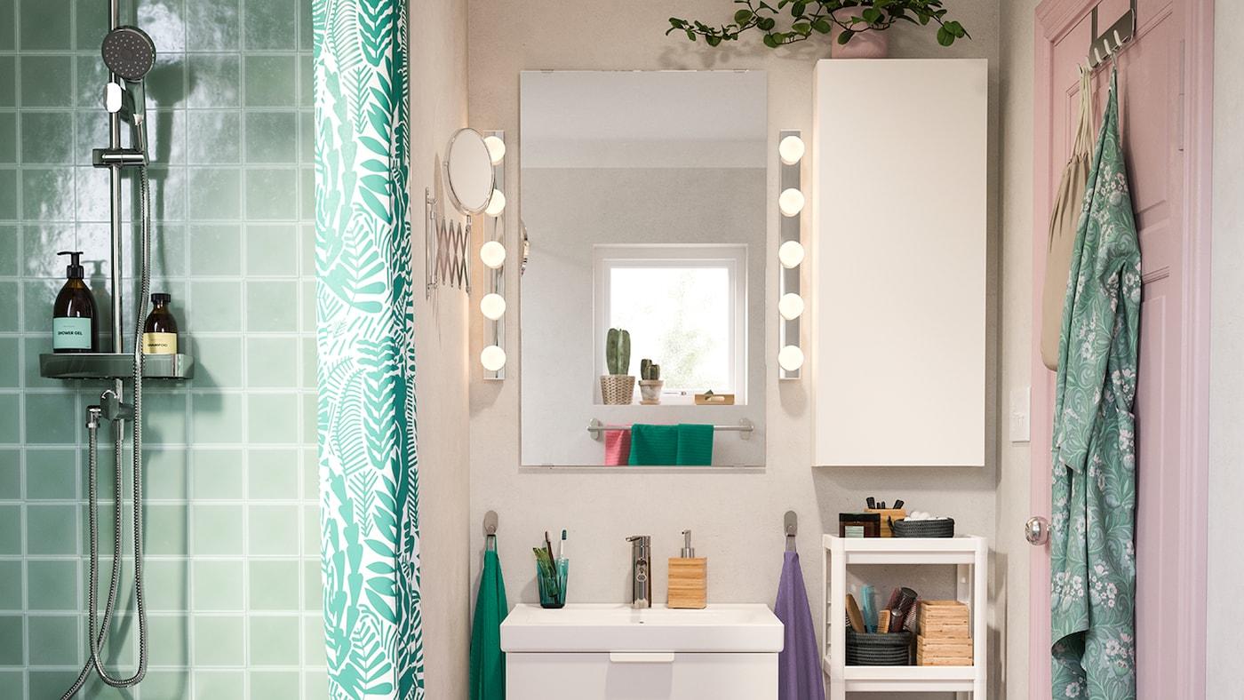 Douche revêtue d'un carrelage vert à côté d'une pièce rose avec un lavabo et une armoire murale de couleur blanche. Deux lampes murales LEDSJÖ allumées.