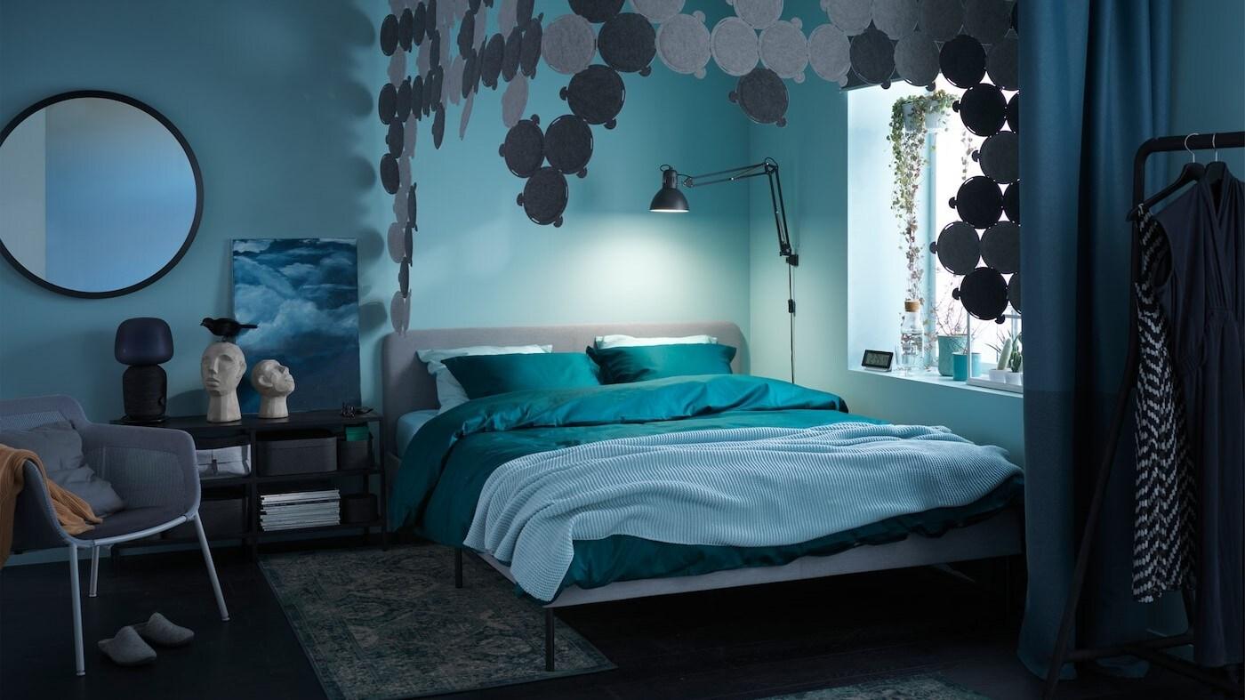 Douillette chambre à coucher dans la pénombre, avec textiles en vert et bleu, panneaux acoustiques et tapis confortables.