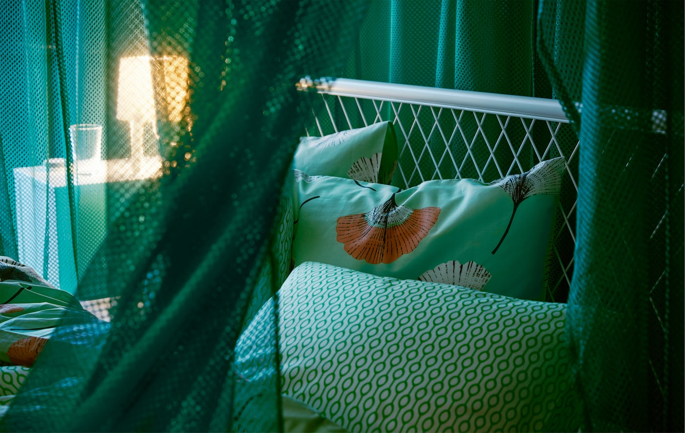 Draped green IKEA GRÅTISTEL net curtains in a bedroom, creating a room in the room, while letting through a little light.