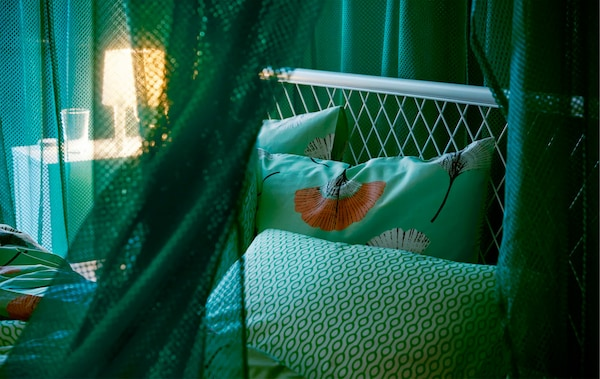 Draped green IKEA GRÅTISTEL net curtains in a bedroom, creating a room in the room, while letting through a little light