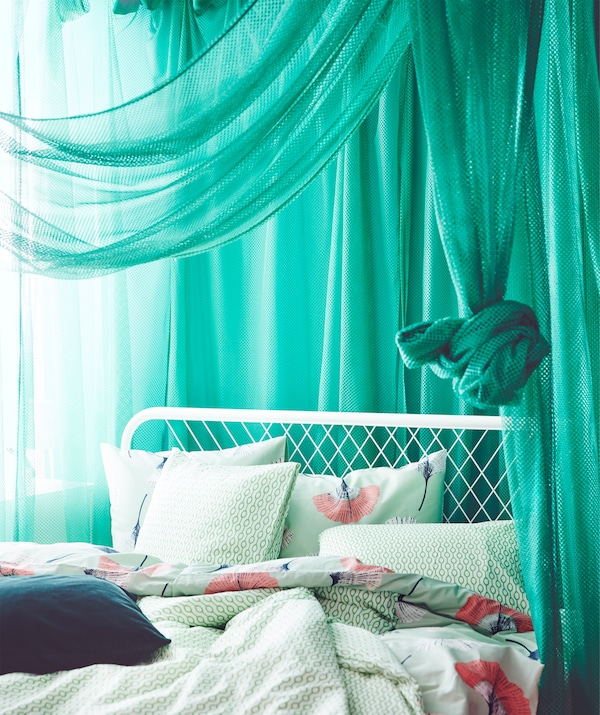 Draped green IKEA GRÅTISTEL net curtains letting through a little light.