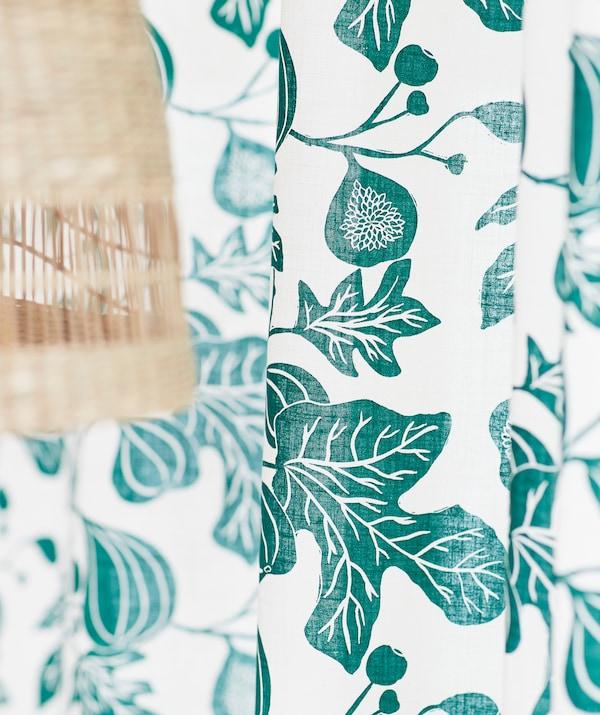 Draperie albă cu imprimeuri verzi reprezentând crengi de smochin, lângă o lustră din fibră naturală de banan.