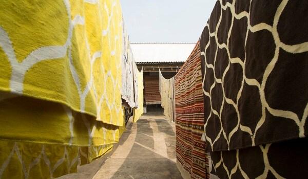 Draussen hängen viele Teppiche mit einem von STOCKHOLM handgefertigten, flachgewebten Teppich in Gelb mit einem Netzmuster.
