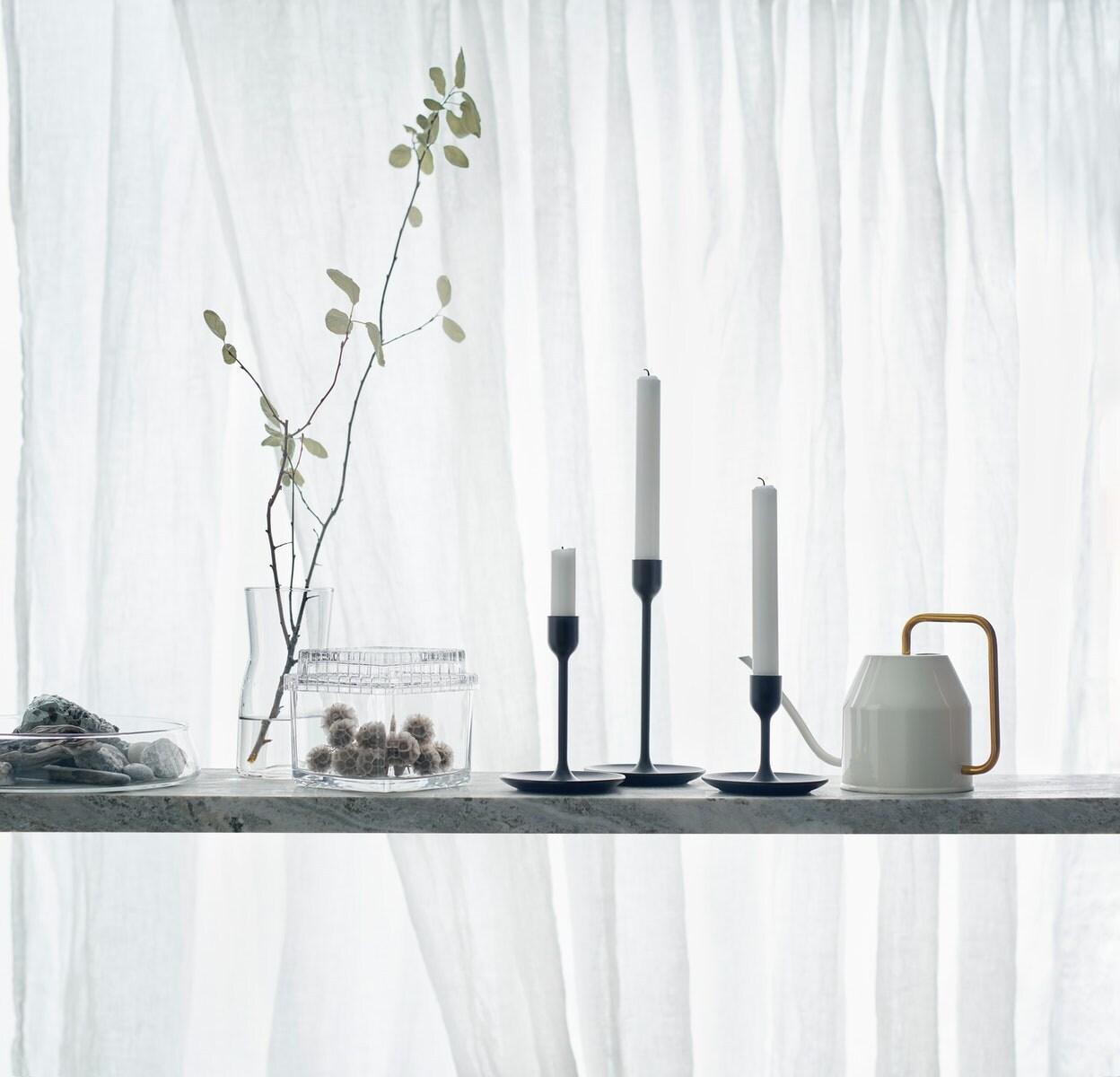 Drei FULLTALIG Kerzenständer in Schwarz in verschiedenen Höhen vor einem weißen Hintergrund, daneben stehen eine Gießkanne und Glasbehälter.