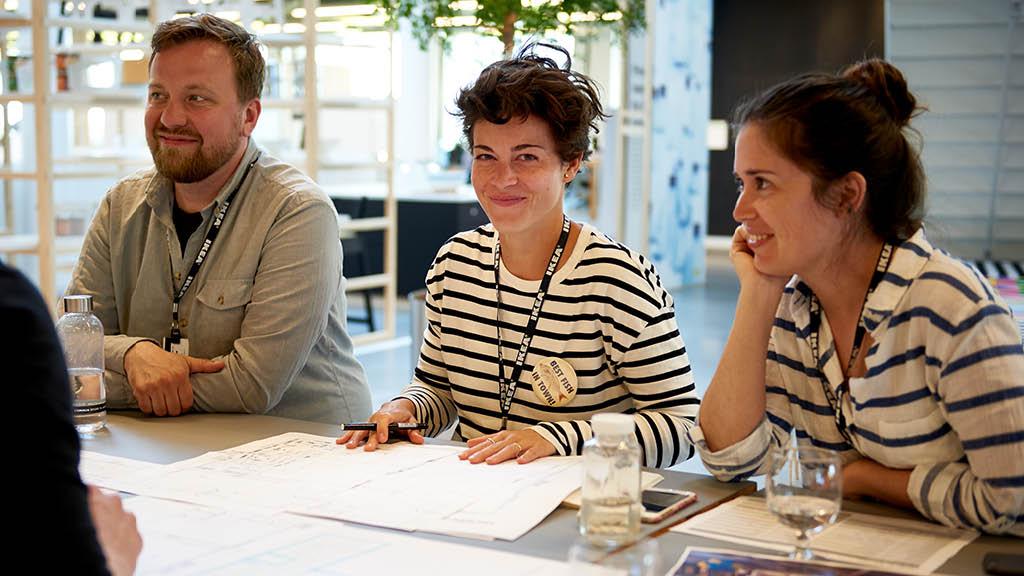 Drei IKEA Mitarbeiter sitzen an einem Tisch in einer Besprechung