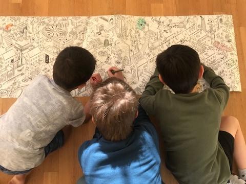 Drei Kinder malen zusammen an einem grossen Ausmalbild