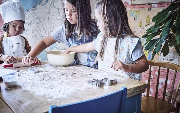 Drei Kinder stehen um einen Tisch mit Mehl, Teig und Backutensilien und backen gemeinsam.