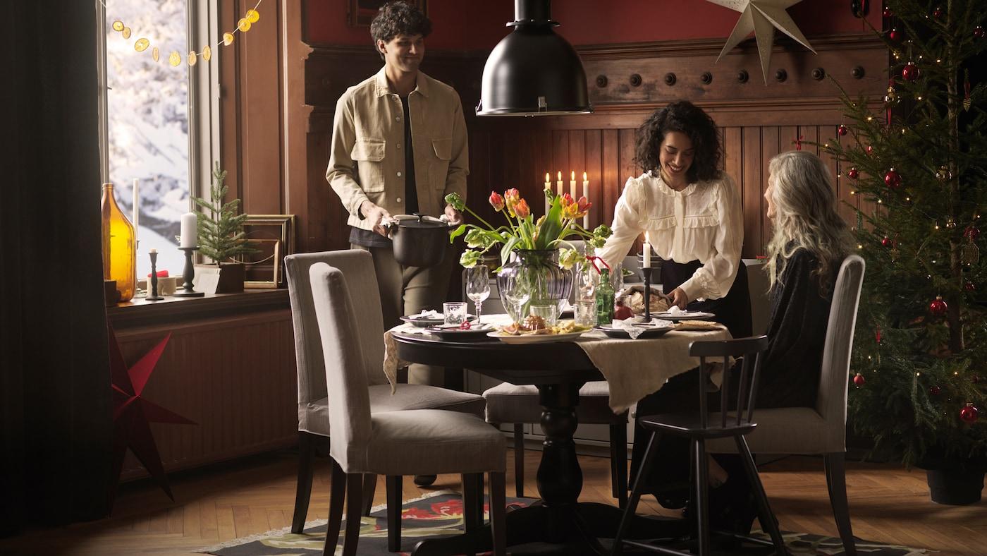 Drei Personen sind um einen runden INGATORP Ausziehtisch in einem festlichen Esszimmer versammelt und essen gemeinsam.