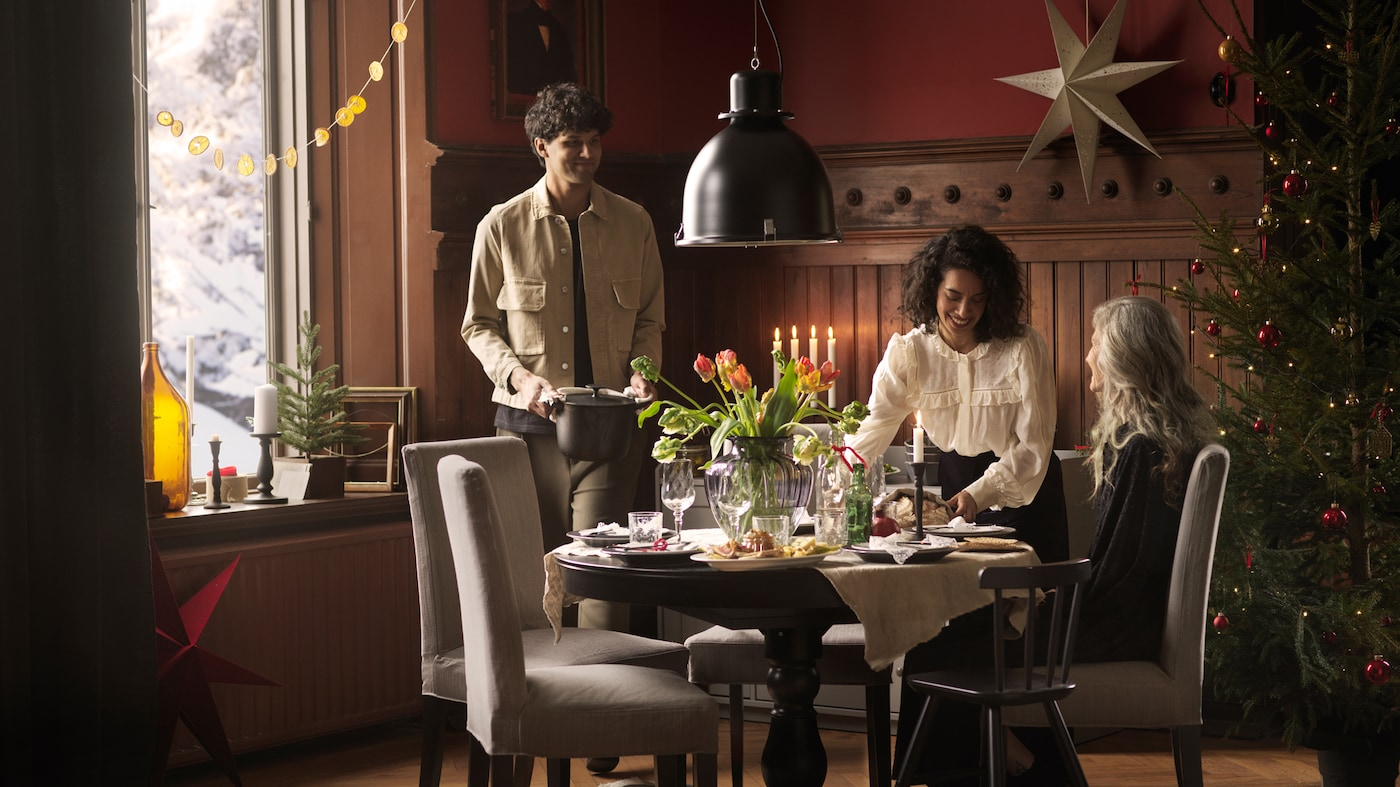 Drei Personen sind um einen runden INGATORP Ausziehtisch versammelt, der mit frischen Blumen geschmückt ist, und essen gemeinsam.