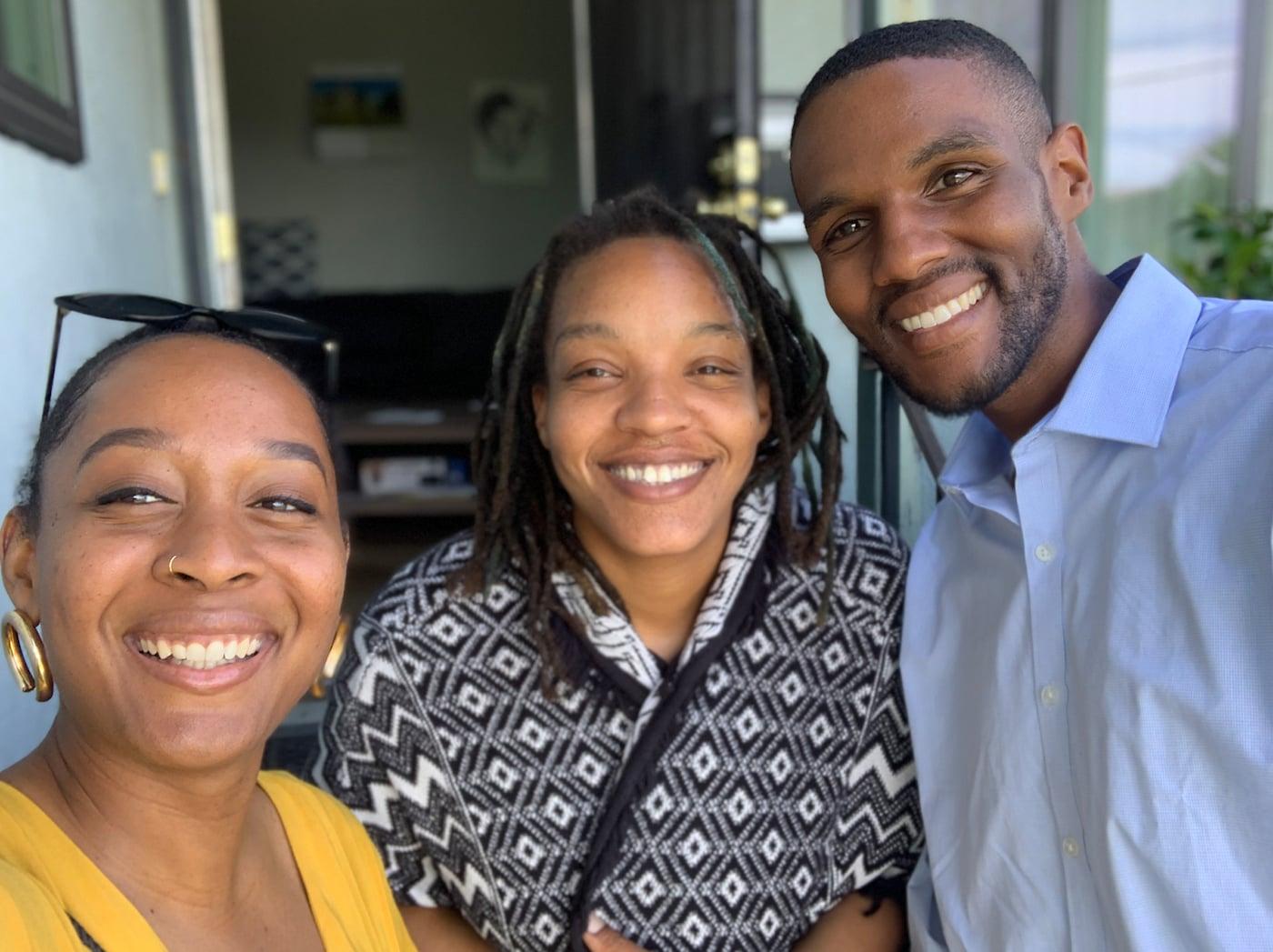 Drei Personen stehen beieinander und posieren lächelnd für ein Foto in ihrem Zuhause.