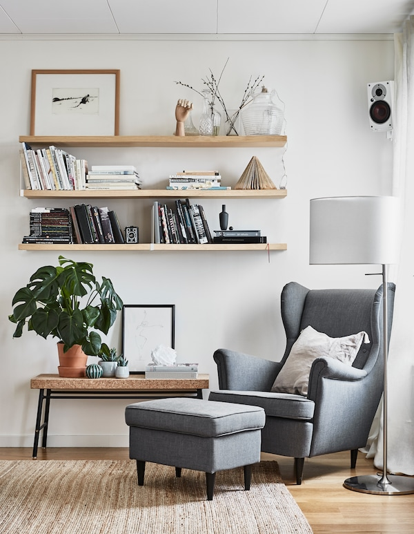 Drei Wandregale und eine Bank in Nähe eines Sessels mit Hocker, u. a. mit STOCKHOLM Standleuchte in Weiß.