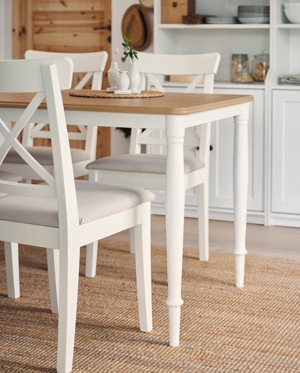 Drei weiße Stühle und ein Tisch in Weiß/Eiche mit gedrehten Beinen aus Stahl stehen auf einem Juteteppich. Im Hintergrund sind zwei weiße Hochschränke zu sehen.