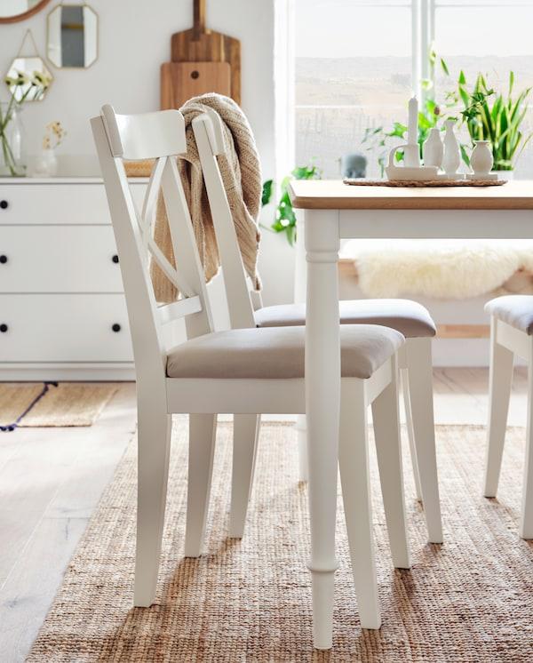 Drei weiße Stühle und ein Tisch in Weiß/Eiche stehen auf einem Juteteppich. Im Hintergrund ist ein Sideboard mit zwei Vasen mit Blumen darin zu sehen.