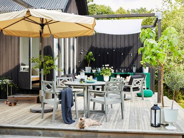 Drevená terasa s béžovým slnečníkom, sivým záhradným nábytkom, stromami v kvetináčoch a mačkou.