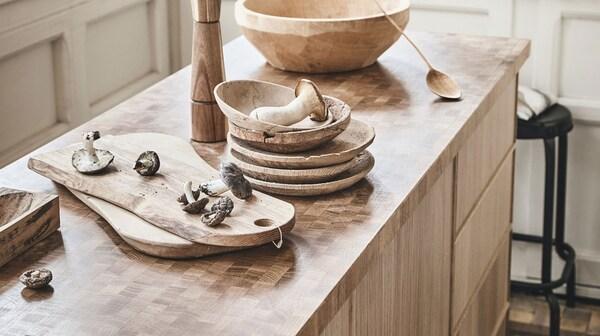 Dřevěné předměty jako misky, naběračka, krájecí desky na pracovní desce IKEA SKOGSÅ s dřevěným povrchem.