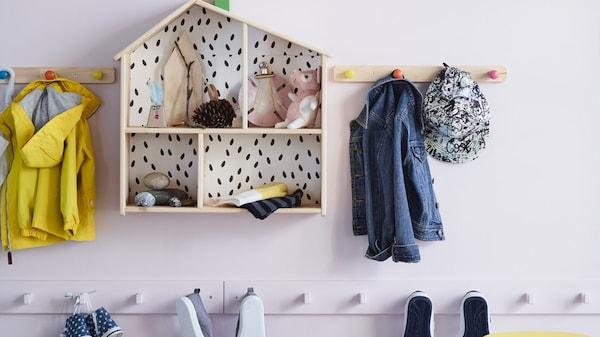 Dřevěný domeček pro panenky a háčky na věšení oblečení, vše připevněné na zdi