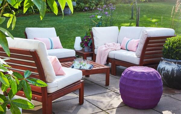 Dřevěný venkovní nábytek s bílými a růžovými polštáři na terase obložené šedou dlažbou