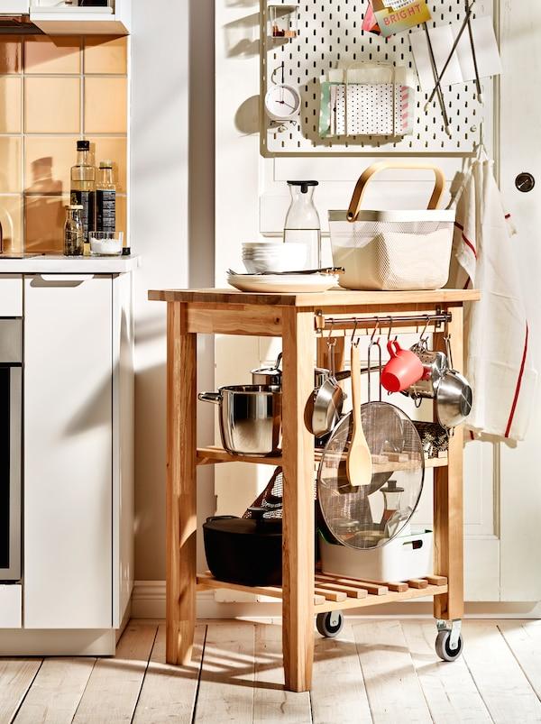 Dřevěný vozík BEKVÄM s hrnci, pánvemi a dalším kuchyňským náčiním. Vozík je postaven tak, že prodlužuje pracovní desku.