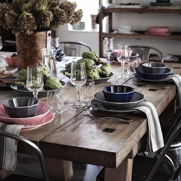 Drewniamy stół nakryty zastawą i dekoracjami.