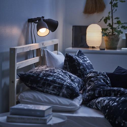 drewniana rama łóżka z materacem i granatową pościelą z lampką nad łóżkiem
