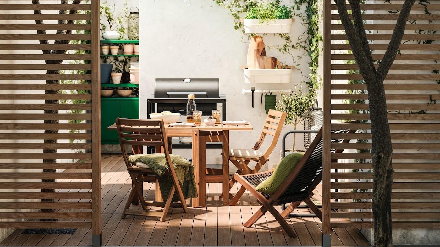 Drewniane przepierzenia, zza których widać patio z drewnianymi meblami, drewnianą podłogą, czarnym grillem i zieloną szafką.