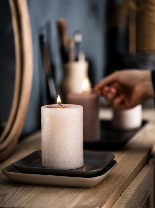 Drewniany kredens w sypialni, na którym ustawiono lustro i ozdoby. Widoczna jest dłoń osoby zapalającej dwie ustawione na kredensie świeczki zapachowe LUGGA.