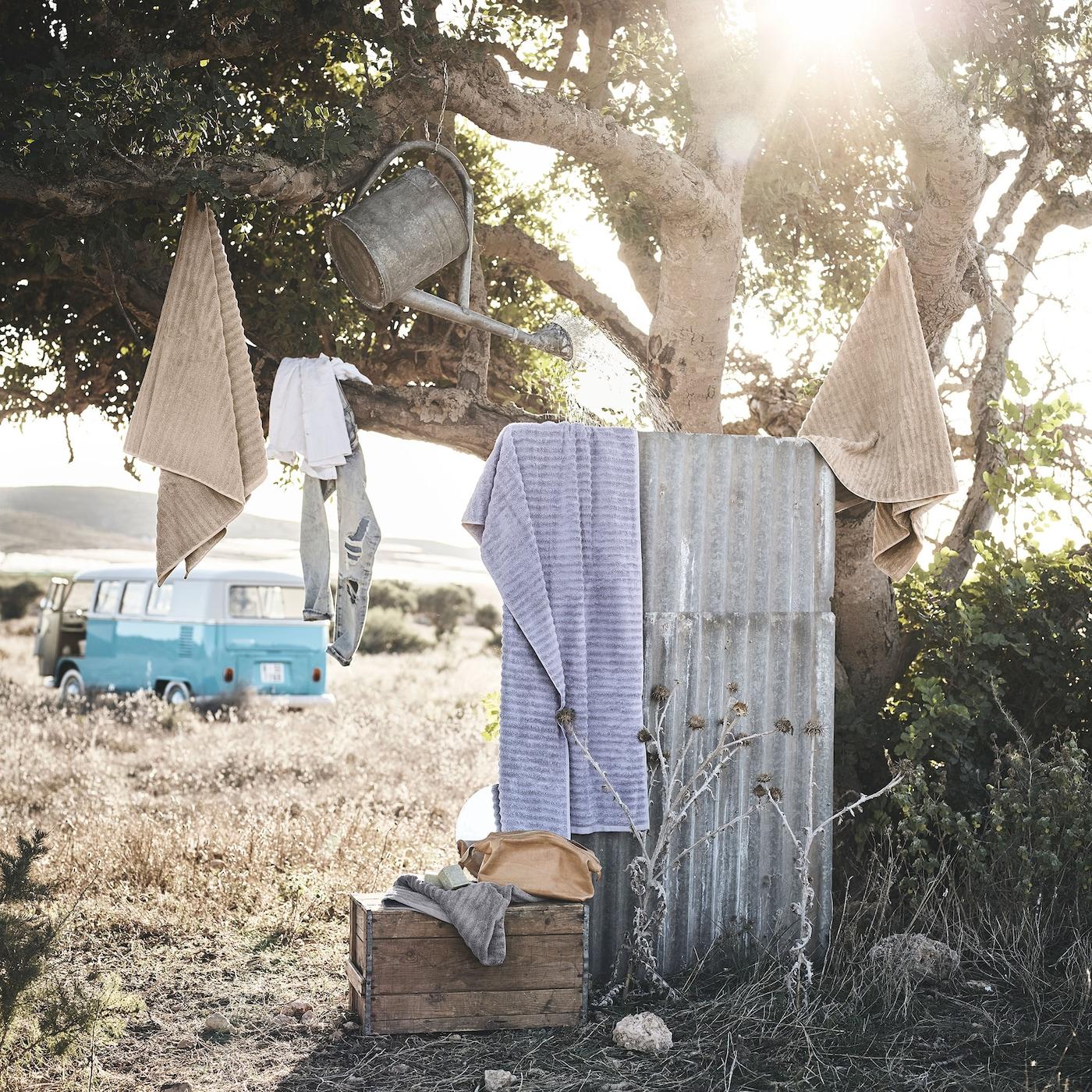 Drie FLODALEN badhanddoeken met golvende textuur in beige en paars katoen hangen in een boom naast een buitendouche.
