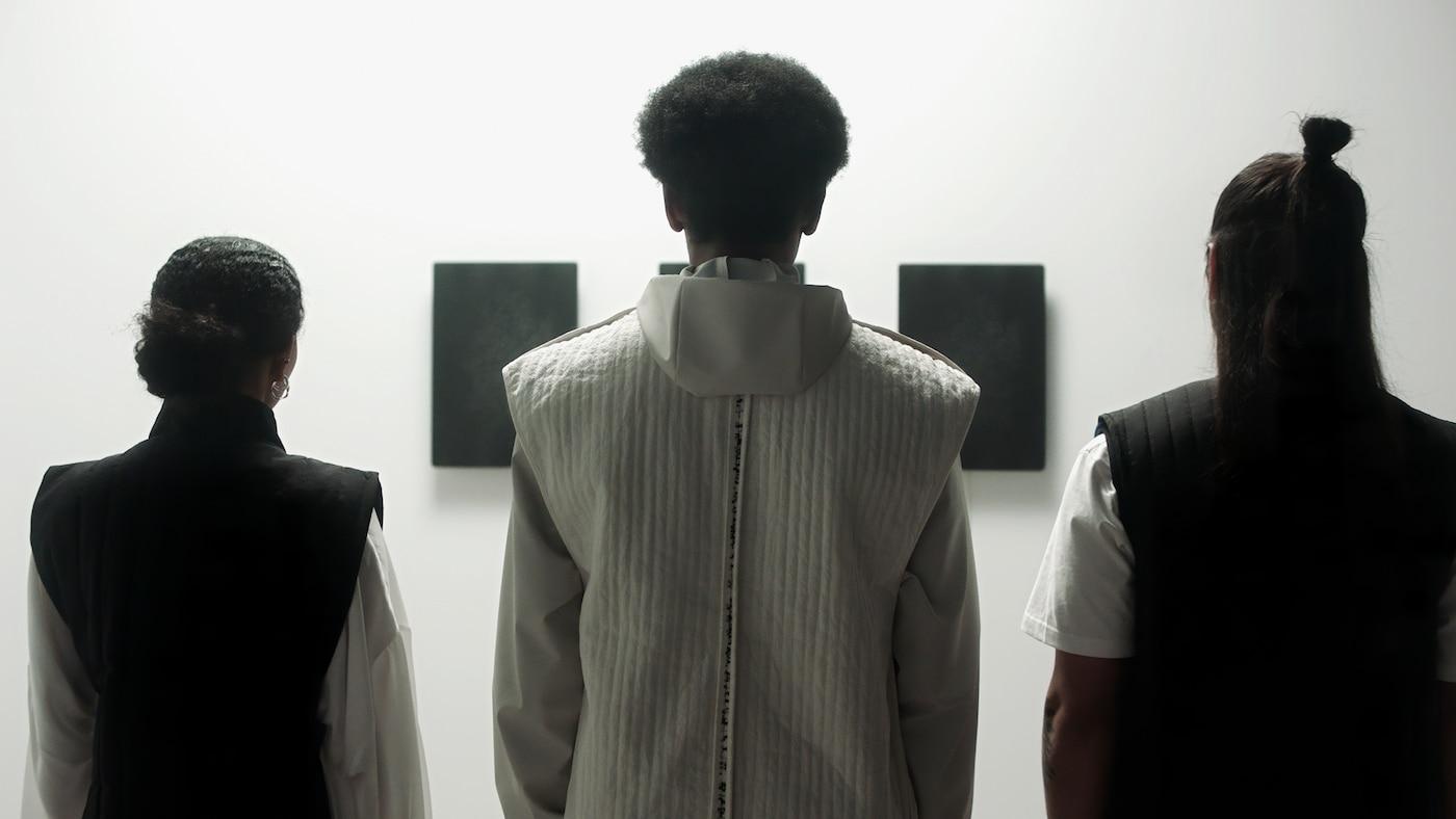 Drie mensen staan voor drie SYMFONISK fotolijsten met wifi-speakers in een witte kamer. De lijsten zijn zwart.