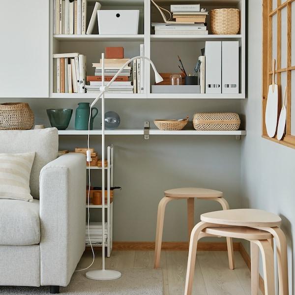 Drie stapelbare KYRRE krukken in berken staan in de hoek van een woonkamer zodat ze extra zitplaatsen kunnen bieden wanneer nodig.