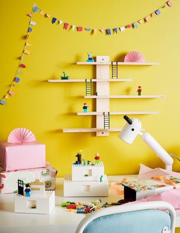Drie witte BYGGLEK dozen staan op het bureau van een kind met LEGO-miniaturen erop en LEGO-stenen er omheen.