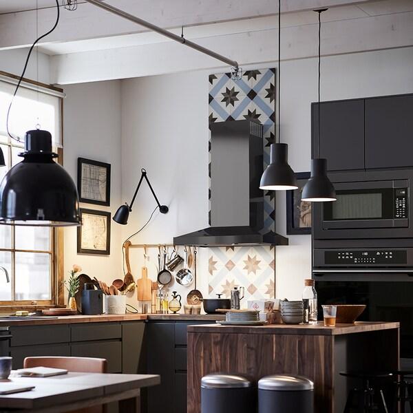 Drie zwarte SVARTNORA hanglampen die bevestigd zijn aan het plafond in een keuken met een strakke vormgeving.